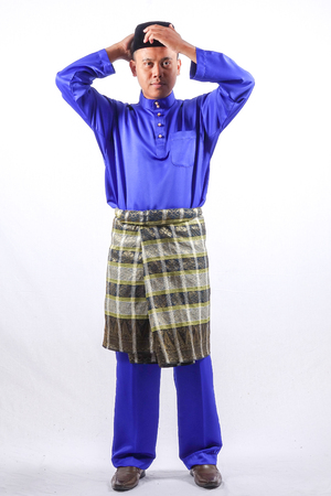 Young asian male with full attire of Baju Melayu (National Custome) for Eid Mubarak celebration Imagens