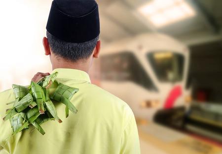 Eid穆巴拉克概念:站立的人等待火车用拿着一束束椰子米饺子。