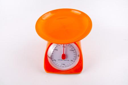 Una balanza de medición de peso de color naranja aislado fondo blanco.