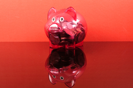 Saving concept with red piggy bank on red background. Stock Photo