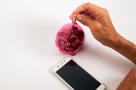 Asian senior inserting notes into a red piggy bank. Saving, retirement plan, retirees financial planning concept