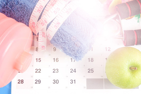 Fitness concept with dumbbell,hand gripper,tower and measuring tape on a calendar background.