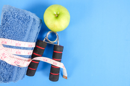 Fitness concept with dumbbell,hand gripper,tower and measuring tape on a blue background. Stock Photo