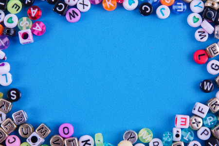 Colorful plastic alphabet dice on a blue background as a background.