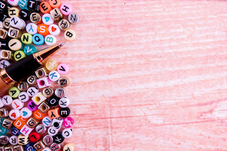 Colorful plastic alphabet dice on a wooden background as a background.