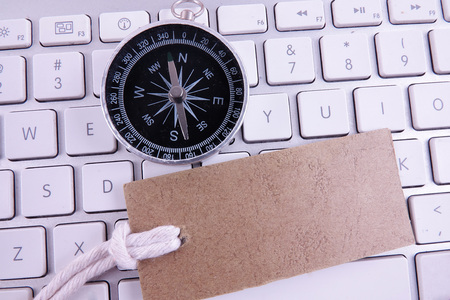 BUSINESS CONCEPT with keyboard, brown tag and compass. Copy space Stock Photo
