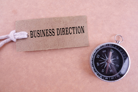 BUSINESS DIRECTION CONCEPT with keyboard, brown tag and compass.