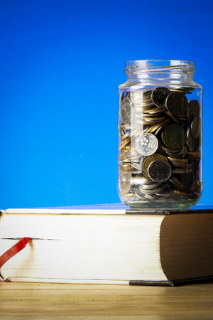 EDUCATION FUND CONCEPT with coins in a glass jar and old book. Banque d'images