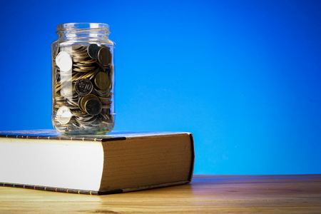 EDUCATION FUND CONCEPT with coins in a glass jar and old book. Standard-Bild