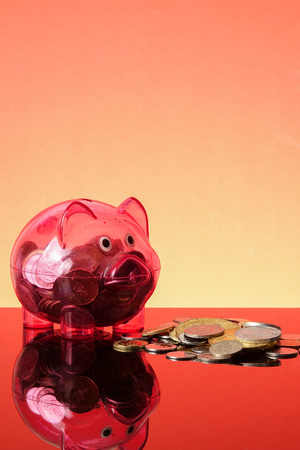SAVING CONCEPT: A red piggy bank on a orange background.