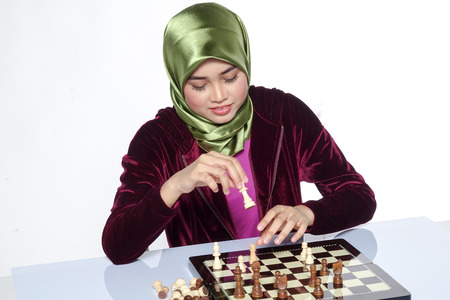 Portrait of a beautiful veiled young woman smiling playing a chess game