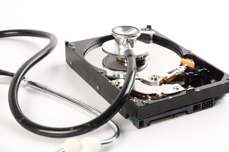 RECOVERY AND REPAIR TECHNOLOGY CONCEPT: Hard Disk Drive (HDD) with stethoscope isolated on white. Archivio Fotografico