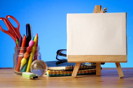 BACK TO SCHOOL CONCEPT: School stationeries over a blue background. Copy Space