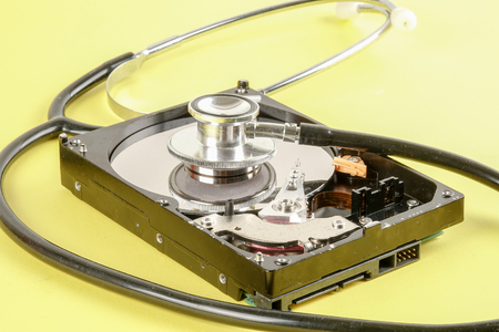RECOVERY AND REPAIR TECHNOLOGY CONCEPT: Hard Disk Drive (HDD) with stethoscope isolated on a yellow background