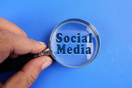 Hand holding magnify glass over a blue background with SOCIAL MEDIA words