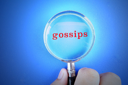 Hand holding magnify glass over a blue background with GOSSIPS words