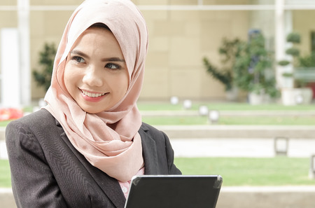 Young muslim woman use smart phone at a garden.