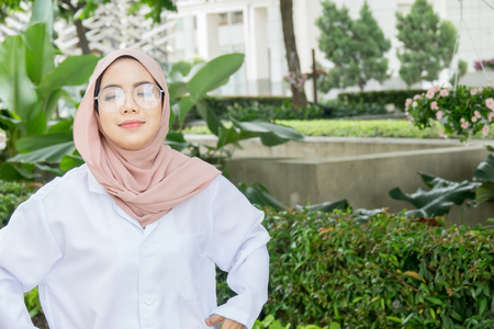 Young female doctor standing at a garden and smiling at camera, health care and prevention concept Reklamní fotografie