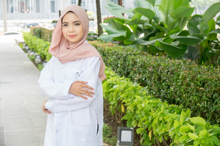 Young female doctor standing at a garden and smiling at camera, health care and prevention concept Imagens