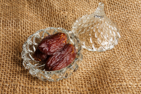 Date in a glass container on a rug background.