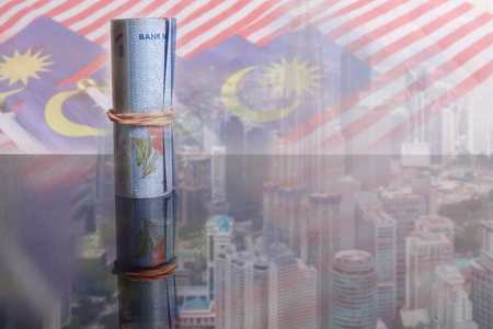 1 Malaysian Ringgit banknotes over a blur background of Malaysia flags and cityscape. Archivio Fotografico
