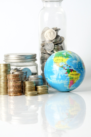Global economy concept with sphere globe and stacked of coins over white. 写真素材