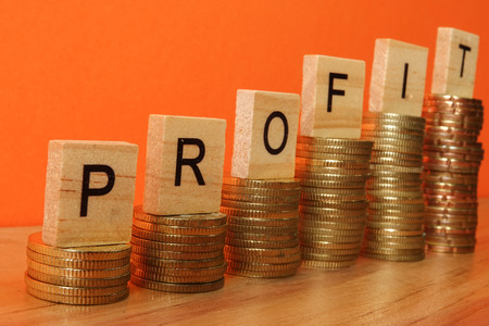 Business concept with PROFIT word on wooden plate onto hike trend stacked of coins. Stock fotó