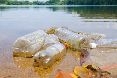 Bad enviromental habit of improper disposal of non-biodegradable PVC cups and bottles in a lake. Selective focus