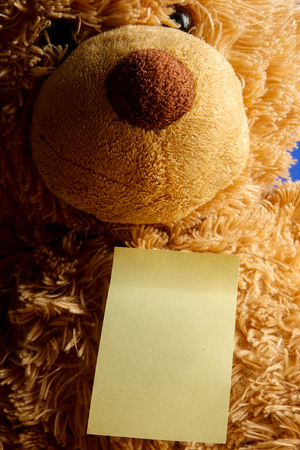 Teddy bear with a yellow stiker on a blue background. Copy space.