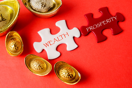 Gold ingots and white puzzle for Chinese New Year festive decorations on a red background. Chinese character means luck,wealth and prosperity as seen in the image. Stock Photo