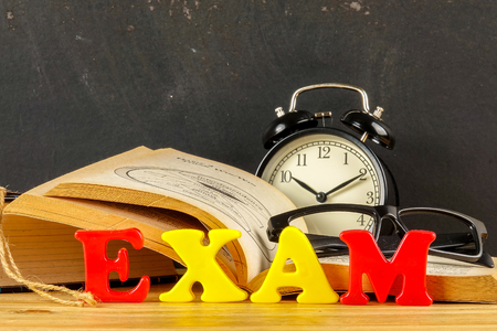 Education concept with books, alarm clock,glass with word EXAM. Stock fotó