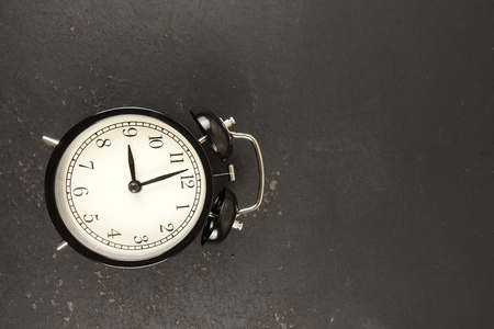 Time Punctuality Concept with black vintage alarm clock.