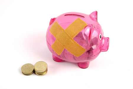SAVING  DETERIORATE CONCEPT. Red piggy bank with bandage and small stack of coins. Standard-Bild - 120778161