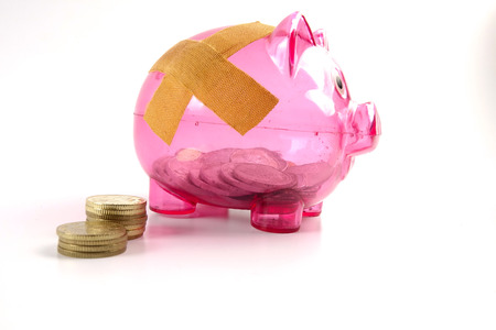 SAVING  DETERIORATE CONCEPT. Red piggy bank with bandage and small stack of coins. Standard-Bild - 120778179