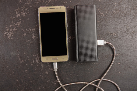 Smartphone and powerbank on rustic black background.