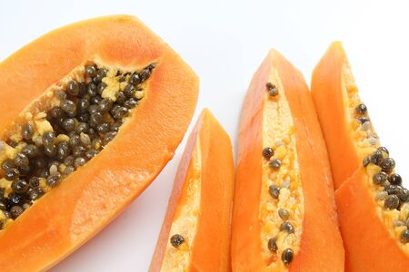 Half and slices papaya isolated on white.