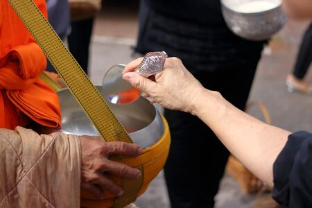 Hands of people while put food to a Buddhist monks alms bowl in  the end of Buddhist Lent Day