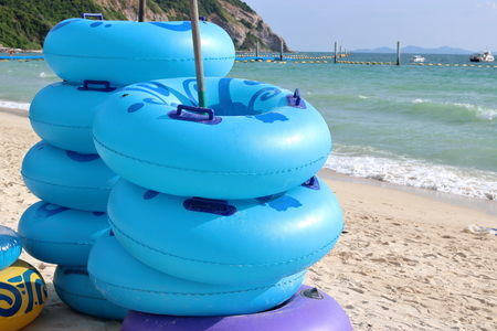 Stack of blue floating rings on the coastline,swim ring, rubber ring, swimming tubes Stock Photo