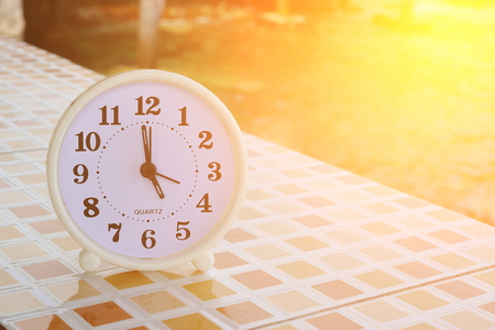White clock at 5pm on the tiled floor and seashore background , Freedom concept , Sunshine effect , Vintage tone