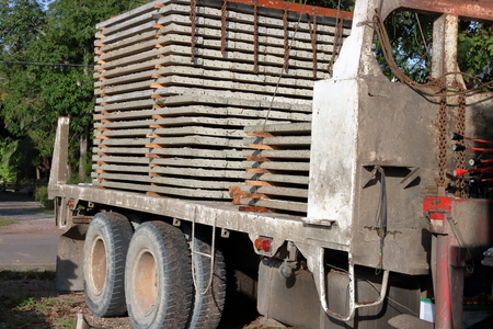 maneuverable: Stack of prestressed concrete slabs loaded on truck for construction, Side view