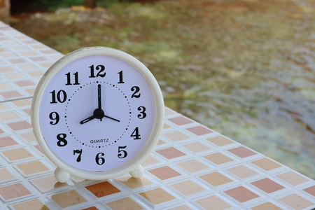 White clock at 8am on the tiled floor and seashore background , Freedom concept Stock Photo