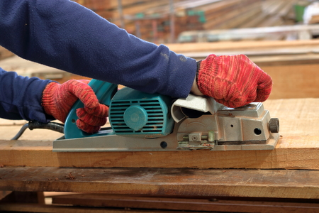 planos electricos: Hand of carpenter using electric planer with wooden plank in carpentry workshop