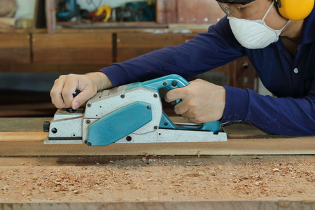 planos electricos: Carpenter using electric planer with wooden plank in carpentry workshop. He is wearing safety equipment