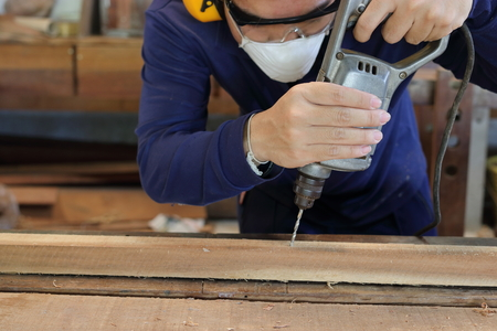 Worker drills a hole using electric drill machine in carpentry workshop. He is wearing safety equipment .