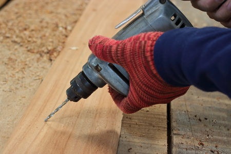 Hand of worker drills a hole with wooden plank using electric drill machine in workshop