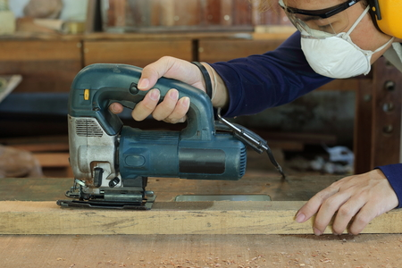 Carpenter is sawing a wooden plank with jig saw machine in carpentry workshop. He is wearing safety equipment.