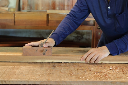 Hand of worker working with a hand planer on  a plank of wood.