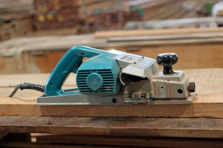 planos electricos: Alisadora eléctrica en el tablón de madera en el taller de carpintería Foto de archivo
