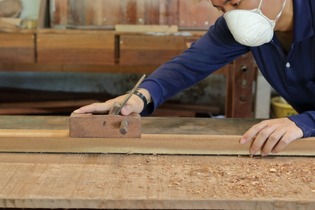 Carpenter working with a hand planer on  a plank of wood in carpentry workshop. He is wearing safety equipment . Stock Photo