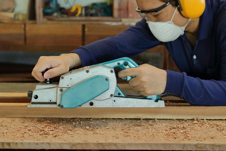 Carpenter using electric planer with wooden plank in carpentry workshop. He is wearing safety equipment